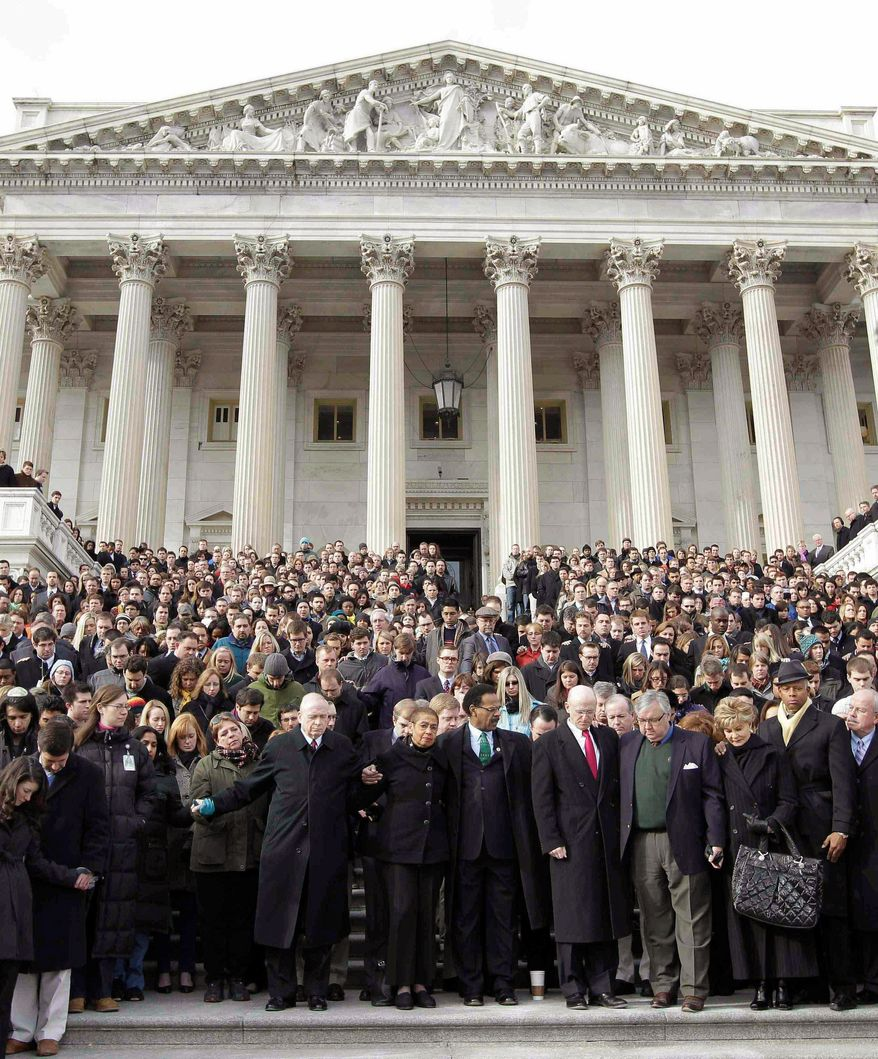 SOLIDARITY: Members of Congress and staffers gather outside the Capitol on Monday to observe a moment of silence for Arizona Rep. Gabrielle Giffords and other victims of the shooting rampage Saturday. (Associated Press)