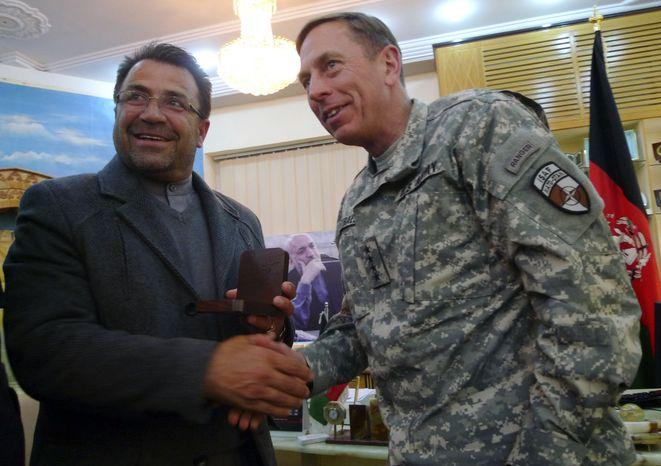 Helmand's Gov. Gulab Mangal, left, shakes hand with U.S. Gen. David Petraeus, NATO's top commander in Afghanistan, in Lashkar Gah, Helmand province, south of Kabul, Afghanistan, Monday, Jan. 10, 2011.  (AP Photo/Heidi Vogt)
