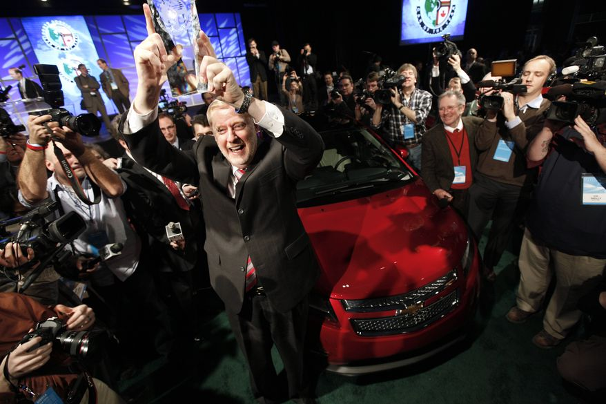 Tom Stephens, vice chairman of General Motors, holds up the North American International Auto Show Car of the Year trophy awarded to the Chevrolet Volt Monday, Jan. 10, 2011. (AP Photo/Paul Sancya)
