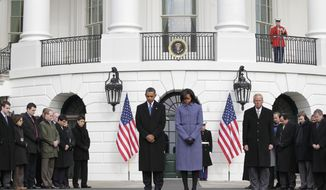 President Obama and first lady Michelle Obama join government employees on the South Lawn of the White House in Washington on Monday, Jan. 10, 2011, to observe a moment of silence for Rep. Gabrielle Giffords and the other victims of an assassination attempt against her. (AP Photo/J. Scott Applewhite)