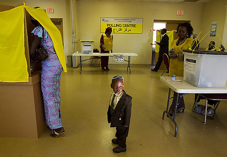 Daniel Chol, 2, looks around as his mother, Josephena Thal, left, of Phoenix, prepares her ballot in a referendum vote on whether South Sudan will become independent from Sudan, at St. James Catholic Church in Glendale, Ariz., on Sunday, Jan. 9, 2011. The polling place in Glendale was one of only eight in the United States. (AP Photo/The Arizona Republic, David Wallace)