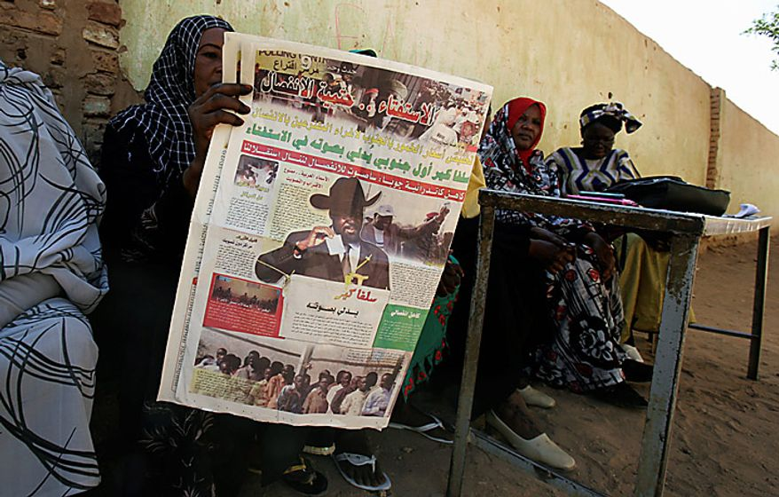 A Southern Sudanese woman reads a newspaper at a polling center during the second day of the independence referendum in the city of Um Durman, Sudan, on Monday, Jan. 10, 2011. Southern Sudan's military spokesman says 20 policemen in the disputed north-south region of Abyei have been killed and 30 more wounded in two attacks by Arab tribesmen and militia. (AP Photo/Abd Raouf)