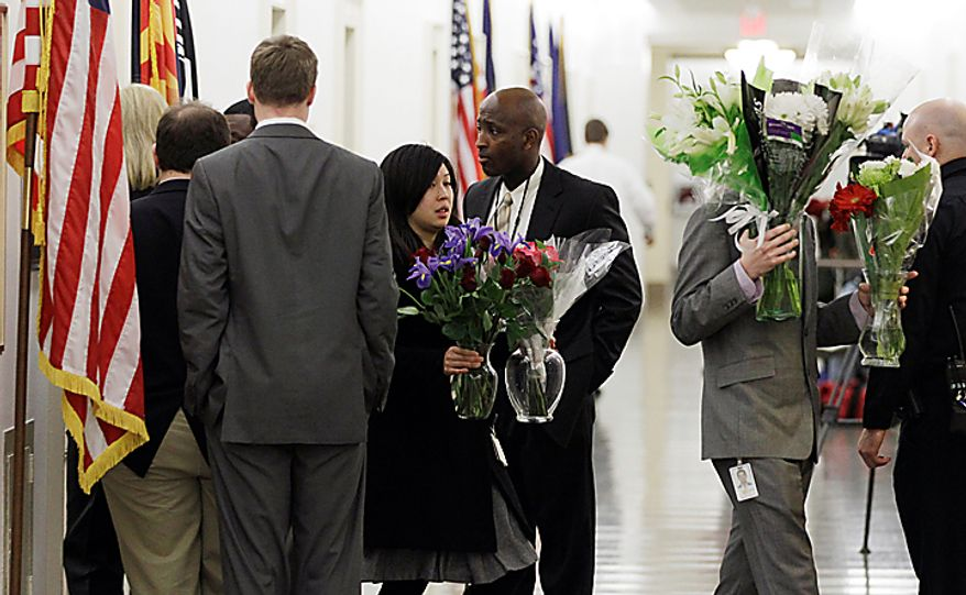 Congressional staffers bring flowers out of the office of Rep. Gabrielle Giffords, Arizona Democrat, in the Longworth House Office Building on Capitol Hill in Washington, Monday, Jan. 10, 2011. Mrs. Giffords was shot Saturday in a Tucson shooting rampage that left six people dead. (AP Photo/Charles Dharapak)