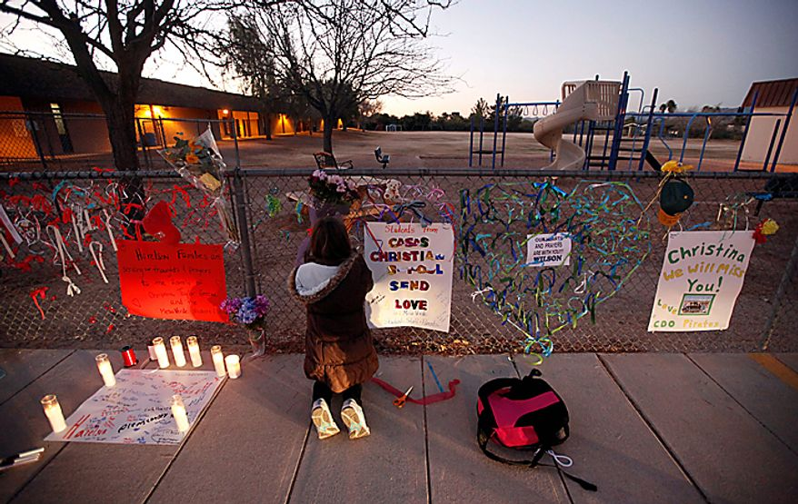 Rachel Cooper-Blackmore, 9, adds a note to a make-shift memorial at Mesa Verde Elementary School in Tucson, Ariz., Monday, Jan. 10, 2011. Christina Green, 9, was shot and killed during an attack at an event for U.S. Rep. Gabrielle Giffords, Arizona Democrat, Saturday. (AP Photo/Chris Carlson)