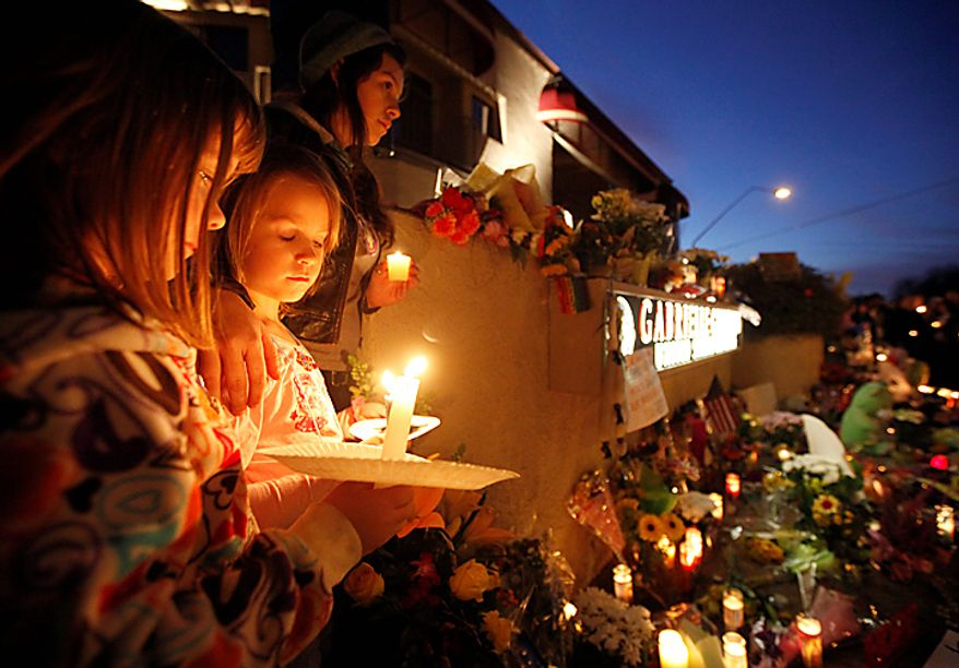 From left, Ellie Steve, 6, Lucia Reeves, 6, and Zoe Reeves, 18, gather for a candlelight vigil outside the offices U.S. Rep. Gabrielle Giffords, Arizona Democrat, in Tucson, Ariz., Sunday, Jan. 9, 2011. Mrs. Giffords was critically wounded during a shooting at a political event Saturday in Tucson. (AP Photo/Chris Carlson)