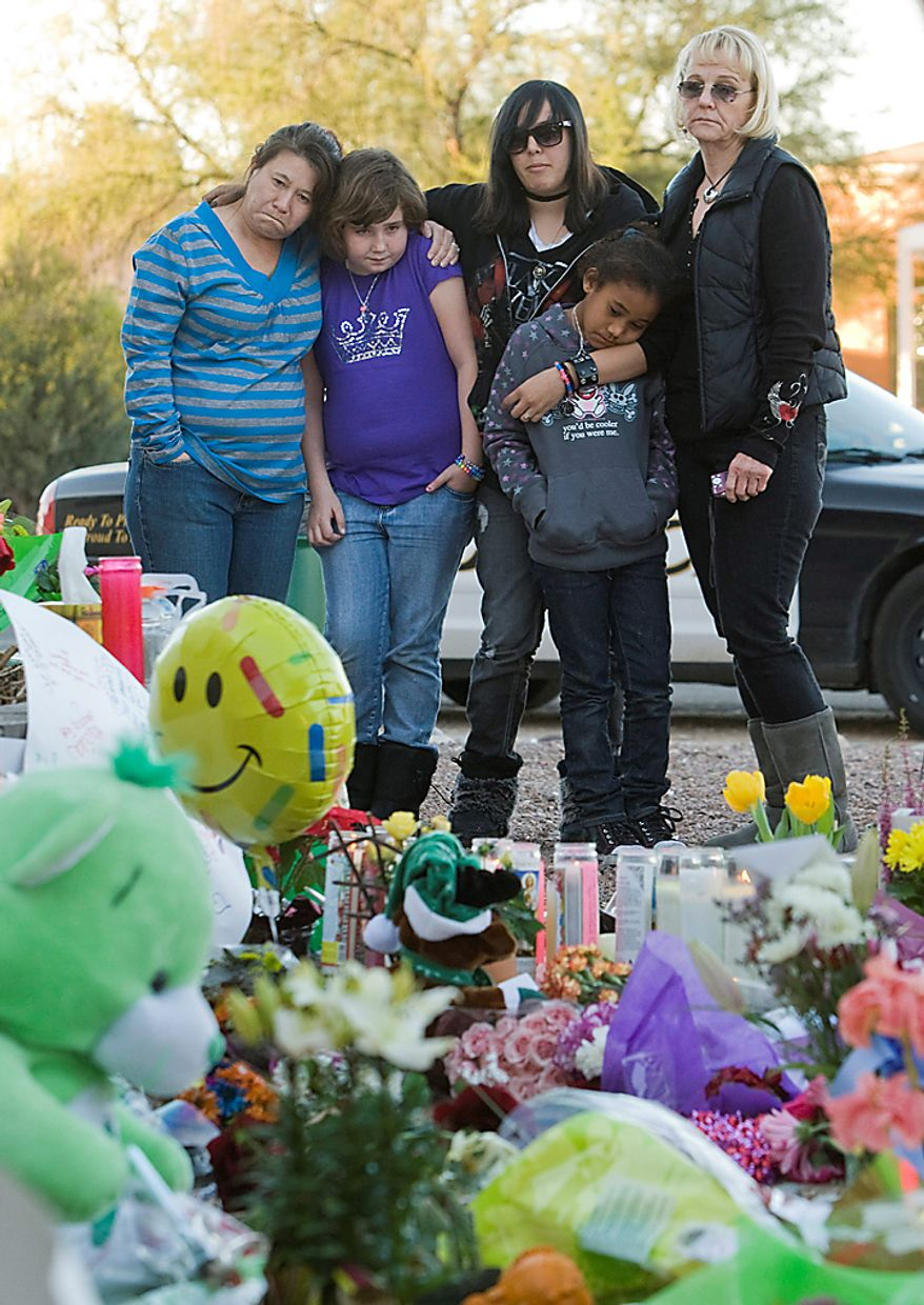 From left, Pam Valentine, Erika Russell, Desi Sloane, Chari Valentine, and Diane Sloane, all from Tucson, pay their respects at a makeshift memorial outside U.S. Rep. Gabrielle Giffords' office in Tucson, Ariz. Sunday, Jan. 9, 2011. A gunman targeting Mrs. Giffords opened fire outside a Safeway in Tucson Saturday, killing six people. (AP Photo/The Arizona Republic, Michael Chow)