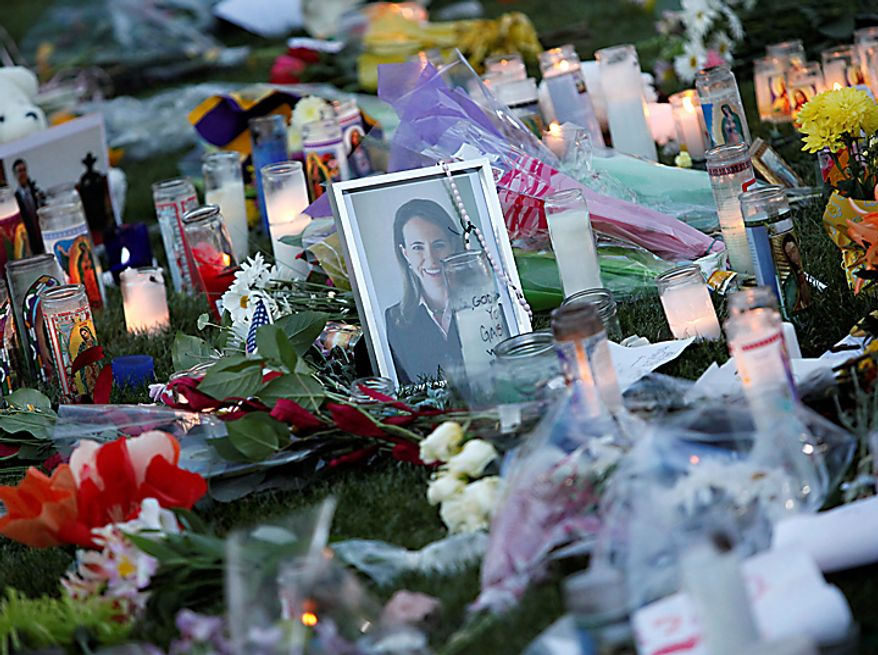Flowers and candles lie on the lawn of University Hospital Sunday, Jan. 9, 2011, in Tucson, Ariz., for U.S. Rep. Gabrielle Giffords, Arizona Democrat, and others who were shot a day earlier during a Giffords speech at a local supermarket. (AP Photo/Matt York)