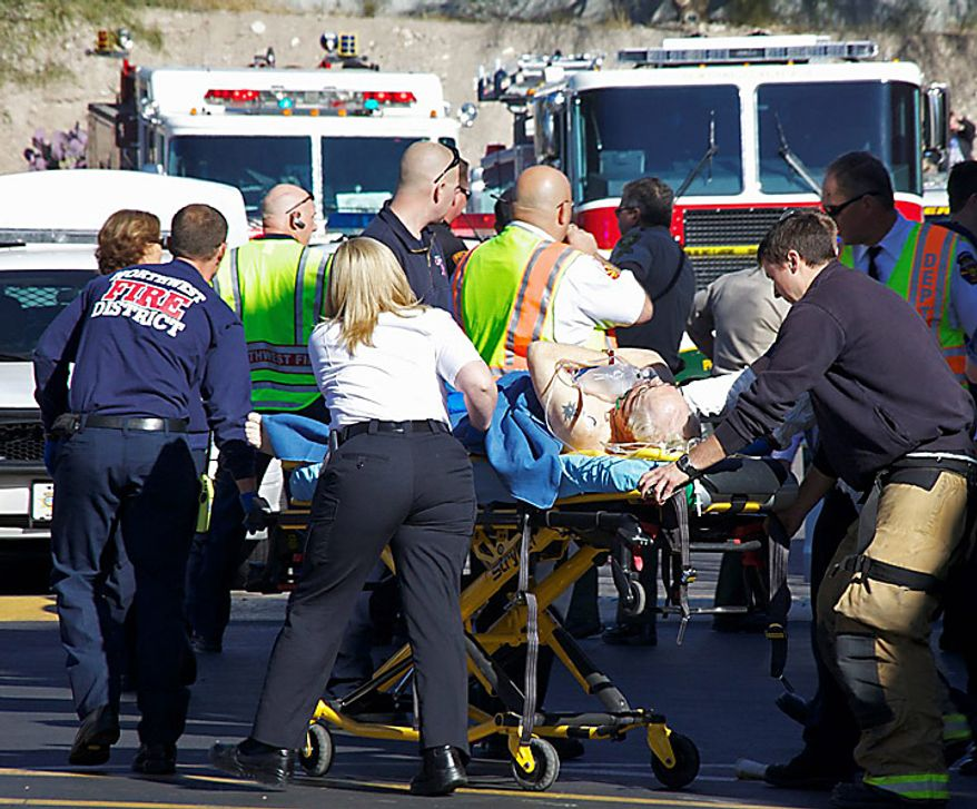 Emergency personnel attend to a shooting victim outside a shopping center in Tucson, Ariz. on Saturday, Jan. 8, 2011, where U.S. Rep. Gabrielle Giffords, Arizona Democrat, and others were shot as the congresswoman was meeting with constituents. (AP Photo/James Palka)