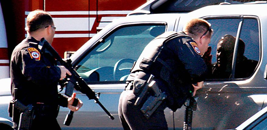 Police search the parking lot outside a Safeway where there has been a shooting involving Rep. Gabrielle Giffords, D-Ariz., on Saturday, Jan. 8, 2011 in Tucson, Ariz.  (AP Photo/Arizona Daily Star, Kelly Presnell)