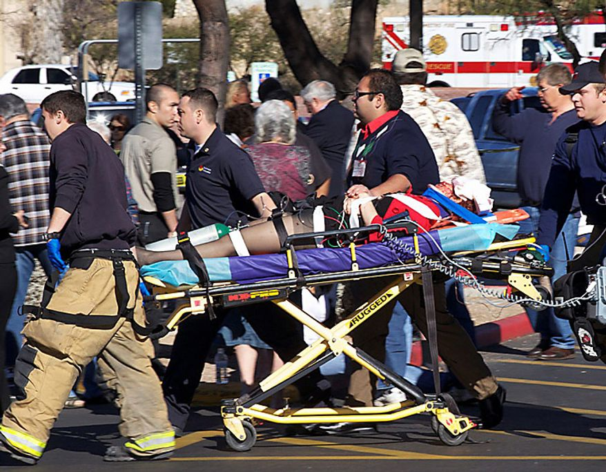 Emergency personnel and Daniel Hernandez, an intern for U.S. Rep. Gabrielle Giffords, second right, move Mrs. Giffords after she was shot in the head outside a shopping center in Tucson, Ariz. on Saturday, Jan. 8, 2011. (AP Photo/James Palka)