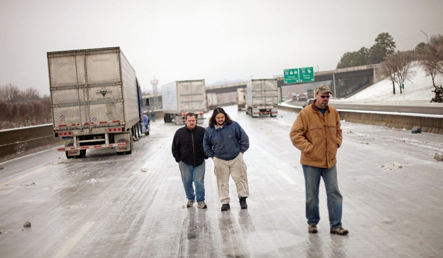 From left, truckers Bill Dougherty, Chis Vlad and Jim Plewinski bide their time on Interstate 285 Tuesday in Atlanta as their trucks sit stranded for 24 hours by a winter storm that turned the road into a sheet of ice. (Associated Press)