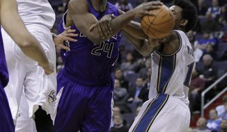 Sacramento Kings forward Carl Landry (24), is fouled by Washington Wizards guard Nick Young (1), during the first quarter of an NBA basketball game on Tuesday, Jan. 11, 2011 in Washington. Also leaping under the basket is Washington Wizards center JaVale McGee (34). (AP Photo/Pablo Monsivais)