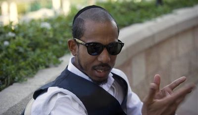 """FILE - In this Thursday, Nov. 11, 2010 file photo, U.S. rapper Jamal """"Shyne"""" Barrow gestures during an interview with The Associated Press in Jerusalem. Reformed rapper and ex-convict Shyne said Tuesday, Jan. 11, 2011 that he is eager to collaborate with artists ranging from young Israeli musicians to hip hop moguls Kanye West and Jay-Z as he revives his career. (AP Photo/Tara Todras-Whitehill, File)"""