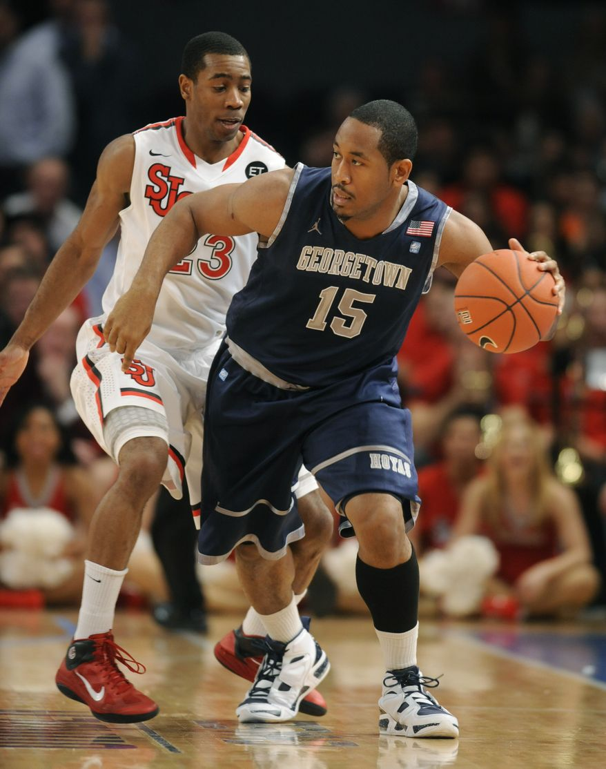 """FILE - In this Jan. 3, 2011 file photo, Georgetown's Austin Freeman, right, handles the ball in front of St. John's Paris Horne in the second half of their NCAA college basketball game at Madison Square Garden in New York. He's the Big East preseason player of the year. He has diabetes. He's a cool customer, calling himself """"ice"""" compared to the """"fire"""" of his fellow senior captain. It's not always easy to get a read on Georgetown's Austin Freeman. (AP Photo/Henny Ray Abrams, File)"""