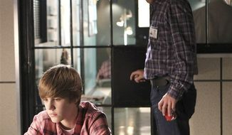 """In this publicity image released by CBS, singer Justin Bieber portrays Jason McCann, left, and George Eads portrays Nick Stokes in a scene from Bieber's acting debut in """"CSI: Crime Scene Investigation.""""  CBS says Justin Bieber is returning as a guest star in an episode of the crime series titled """"Targets of Obsession,"""" scheduled for broadcast Feb. 17, 2011. (AP Photo/CBS, Sonja Flemming)"""