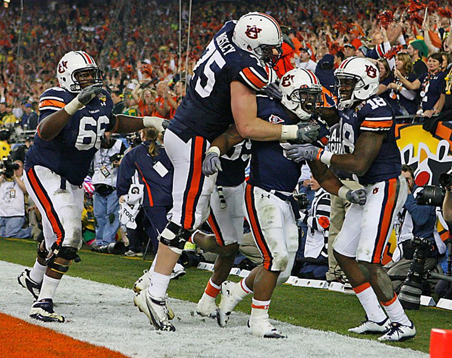 Auburn players celebrate after taking the ball to the 1-yard line on the final drive against Oregon during the BCS championship NCAA college football game on Monday, Jan. 10, 2011, in Glendale, Ariz. Auburn defeated Oregon, 22-19. (AP Photo/The Arizona Republic, David Kadlubowski)