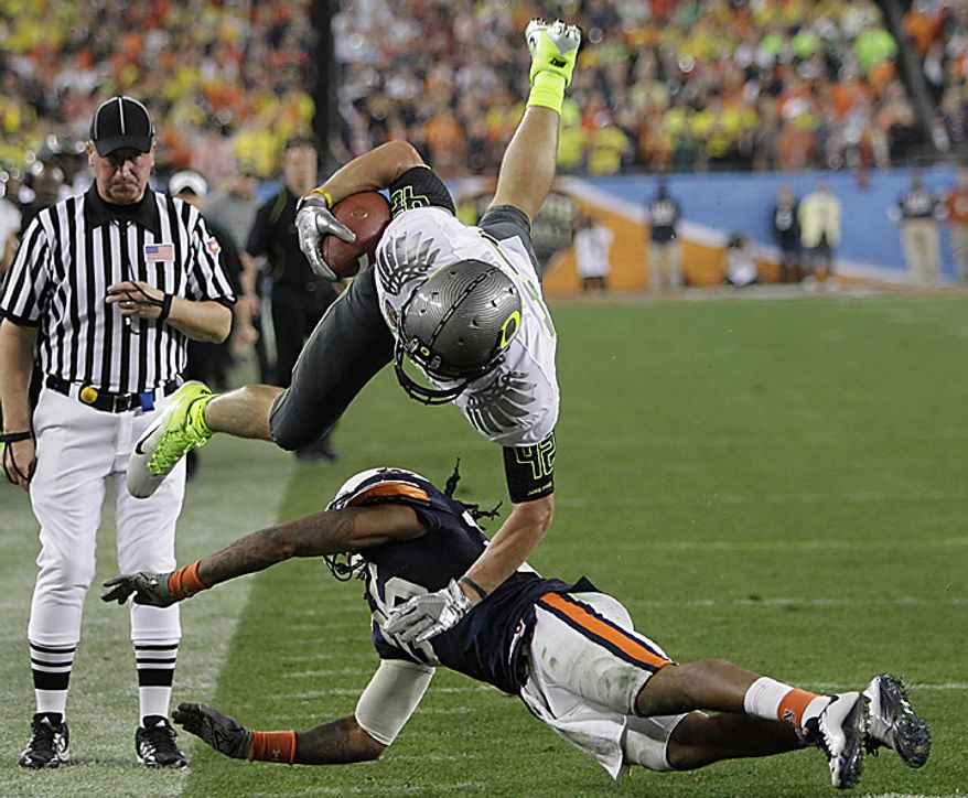 Oregon's David Paulson (42) is upended by Auburn's Mike McNeil during the second half of the BCS national championship NCAA college football game on Monday, Jan. 10, 2011, in Glendale, Ariz. (AP Photo/Matt York)