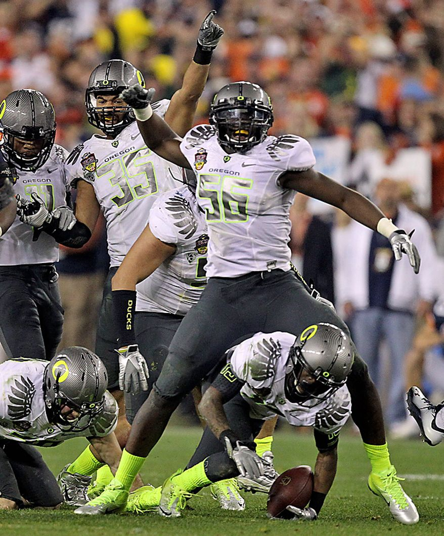 Oregon's Josh Kaddu (56) and Spencer Paysinger (35) celebrate after teammate Cliff Harris, bottom, recovered an Auburn fumble during the second half of the BCS national championship NCAA college football game on Monday, Jan. 10, 2011, in Glendale, Ariz. (AP Photo/Chris Carlson)