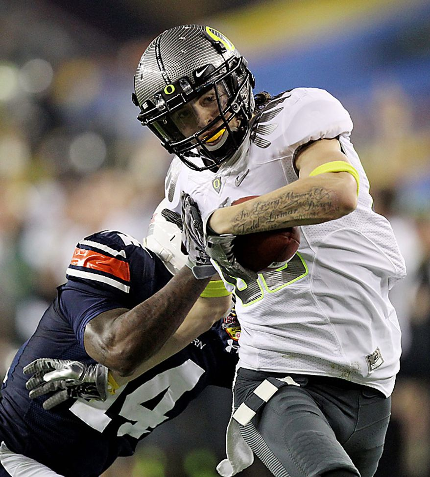 Oregon's Jeff Maehl fends off Auburn's Demond Washington, left, on an 81-yard pass play during the first half of the BCS national championship NCAA college football game on Monday, Jan. 10, 2011, in Glendale, Ariz. (AP Photo/Chris Carlson)