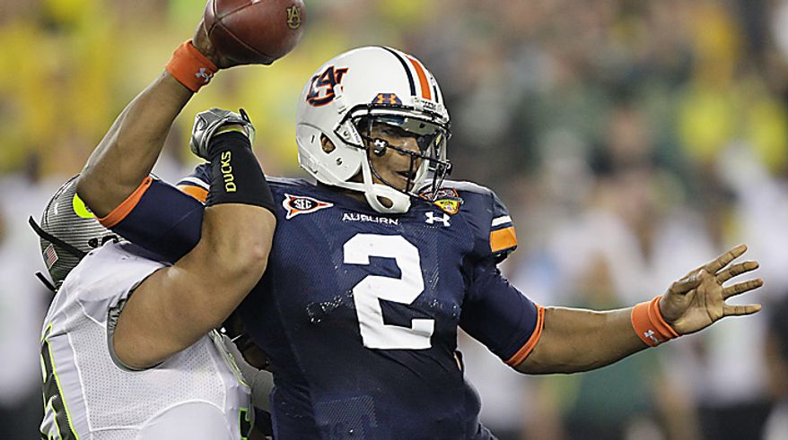 Oregon's Zac Clark, left, sacks Auburn's Cam Newton during the first half of the BCS national championship NCAA college football game on Monday, Jan. 10, 2011, in Glendale, Ariz. (AP Photo/Matt York)