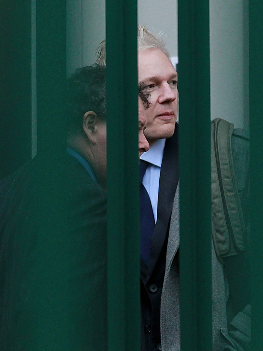 WikiLeaks founder Julian Assange, right, arrives at Belmarsh Magistrate's court in London for his extradition hearing, Tuesday, Jan. 11, 2011. (AP Photo/Matt Dunham)