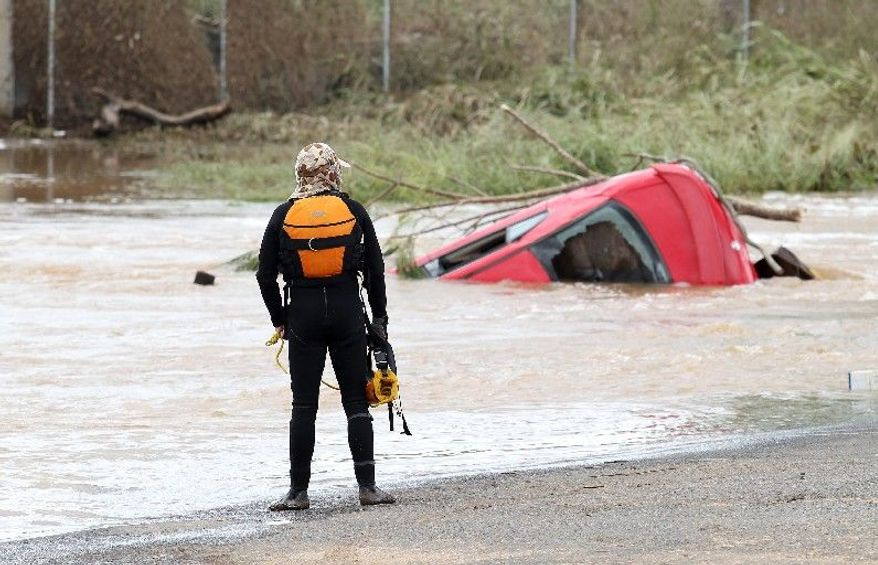 A police diver watches a car wreck outside the town of Grantham in South East Queensland, Australia, on Wednesday. The small town was hit by flash flooding causing mass destruction. (Associated Press)