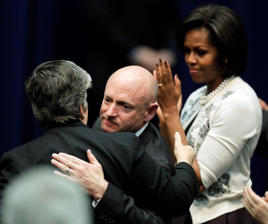 First lady Michelle Obama watches as astronaut Mark Kelly, husband of Rep. Gabrielle Giffords, hugs Homeland Security Secretary Janet Napolitano on Wednesday in Tucson, Ariz., at a memorial service for victims of Saturday's shootings. (Associated Press)