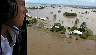 Australia's New South Wales state Premier Kristina Keneally looks at flooded homes at Lawrence, Wednesday, Jan. 12, 2011. Deadly floodwaters that have cut a swath across northeastern Australia flowed onto the streets of the nation's third-largest city, Brisbane, forcing people to flee suburbs and skyscrapers. (AP Photo/Wolter Peeters, Pool)