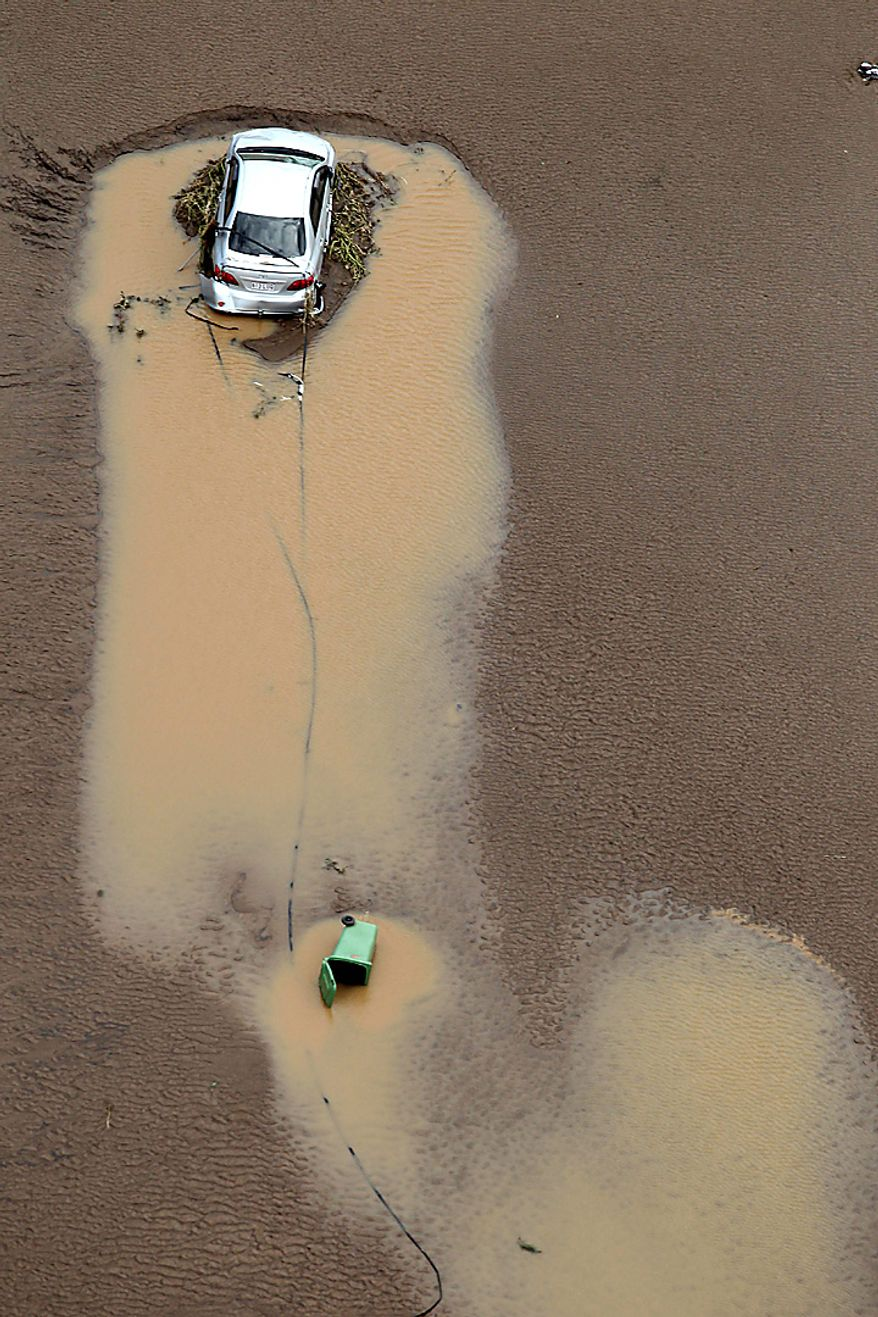 A vehicle is swept away in floodwaters in South East Queensland, Wednesday, Jan. 12, 2011. Deadly floodwaters flowed onto the streets in Australia's northeastern state of Queensland since drenching rains that began in November sent swollen rivers spilling over their banks, inundating an area larger than France and Germany combined. (AP Photo)