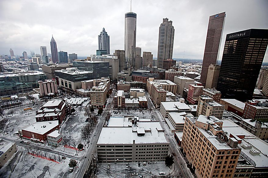 Downtown Atlanta stands covered in snow and ice Tuesday, Jan. 11, 2011. A winter storm left many parts of Georgia crippled for a second day Tuesday, stranding Greyhound bus passengers in Atlanta without food and closing down government offices and school districts as roads remained coated in snow and ice. (AP Photo/David Goldman)