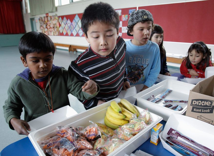 Second-grader Jonathan Cheng (center) looks over fruits and vegetables in the cafeteria at Fairmeadow Elementary School in Palo Alto, Calif. School lunch rules proposed by the U.S. Agriculture Department would limit calories allowed in school meals while increasing whole grains, fruits and vegetables. (Associated Press)