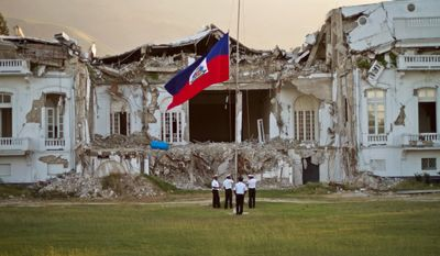 Haitian police lower the national flag Wednesday in front of the still-damaged presidential palace on the first anniversary of the magnitude-7.0 earthquake in Port-au-Prince. The poverty-stricken country also has presidential election problems. (Associated Press)