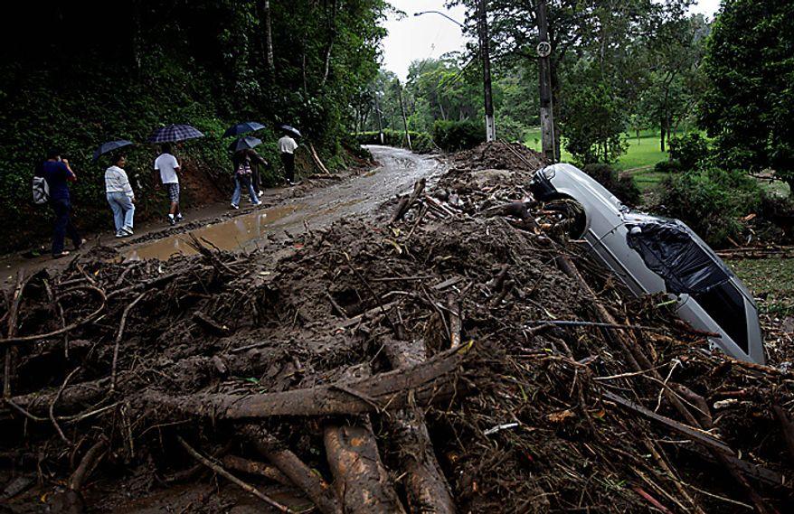 People walk next to debris and a damaged car after landslides in the Caleme neighborhood in Teresopolis, Brazil, Thursday, Jan. 13, 2011. (AP Photo/Felipe Dana)