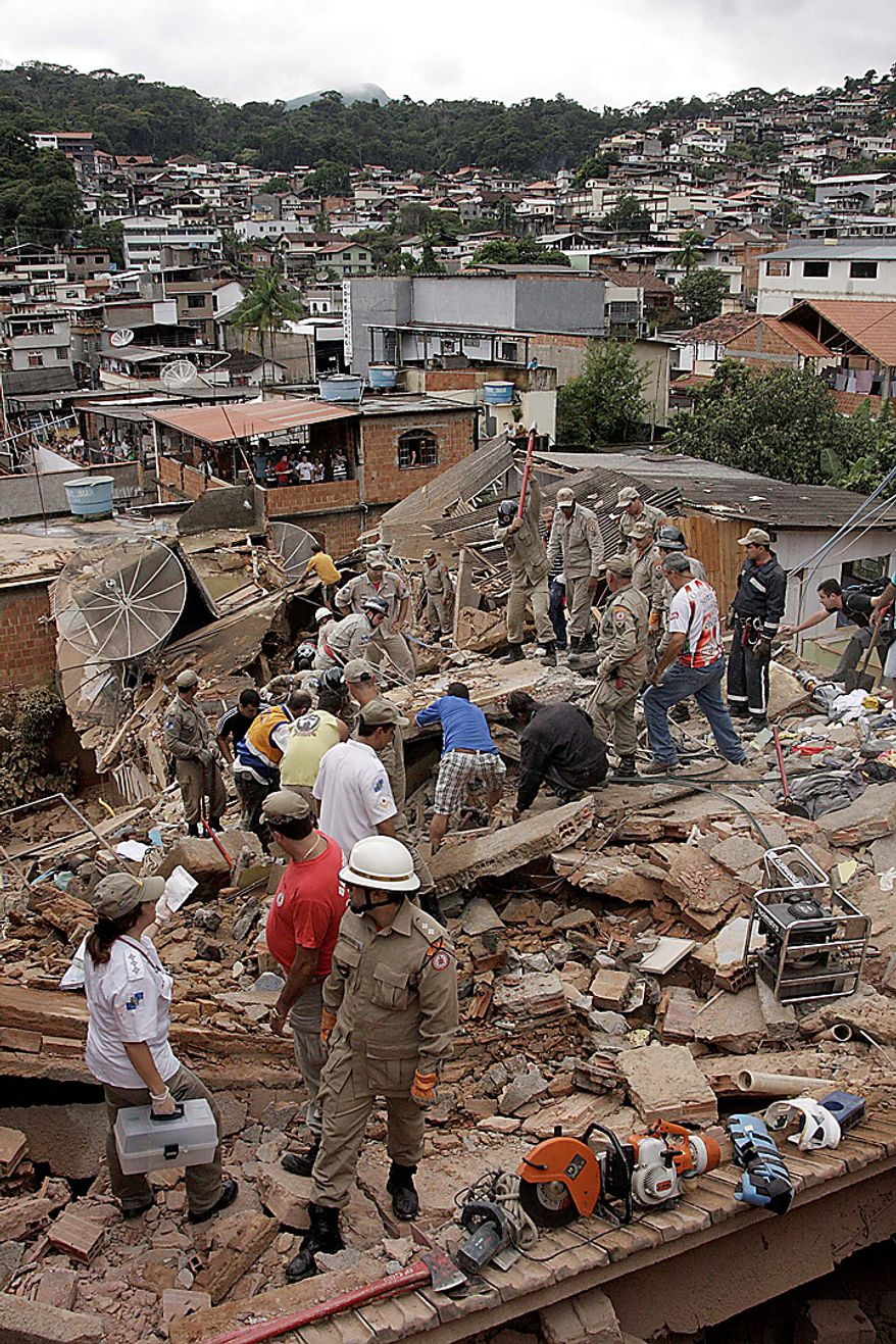 Rescue workers search for survivors in collapsed homes destroyed by flooding in the Nova Friburgo municipality of Rio de Janeiro state, Brazil, Wednesday Jan. 12, 2011. Torrential summer rains tore through Rio de Janeiro state's mountains, killing more than 300 people. (AP Photo/Gerson Goncalo, Agencia O Dia)