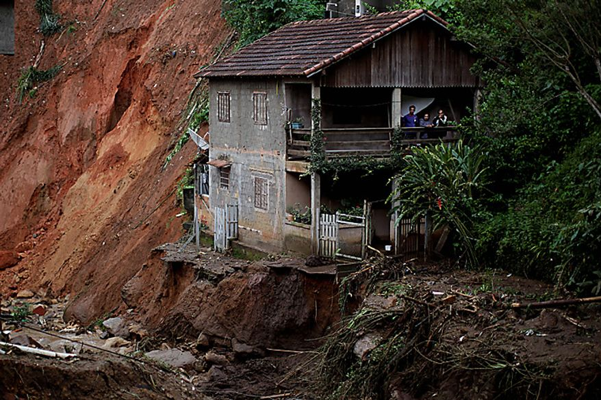 People stand on the porch of their home at the edge of landslide damage in the Caleme neighborhood in Teresopolis, Brazil, Thursday, Jan. 13, 2011. (AP Photo/Felipe Dana)