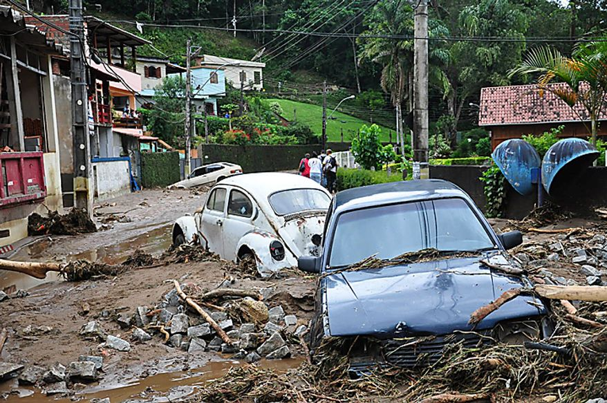 Cars sit in debris in a flooded street in Teresopolis, Rio de Janeiro state, Brazil, Wednesday Jan. 12, 2011.  Torrential summer rains tore through Rio de Janeiro state's mountains, killing more than 300 people. (AP Photo/Roberto Ferreira, Agencia O Dia)