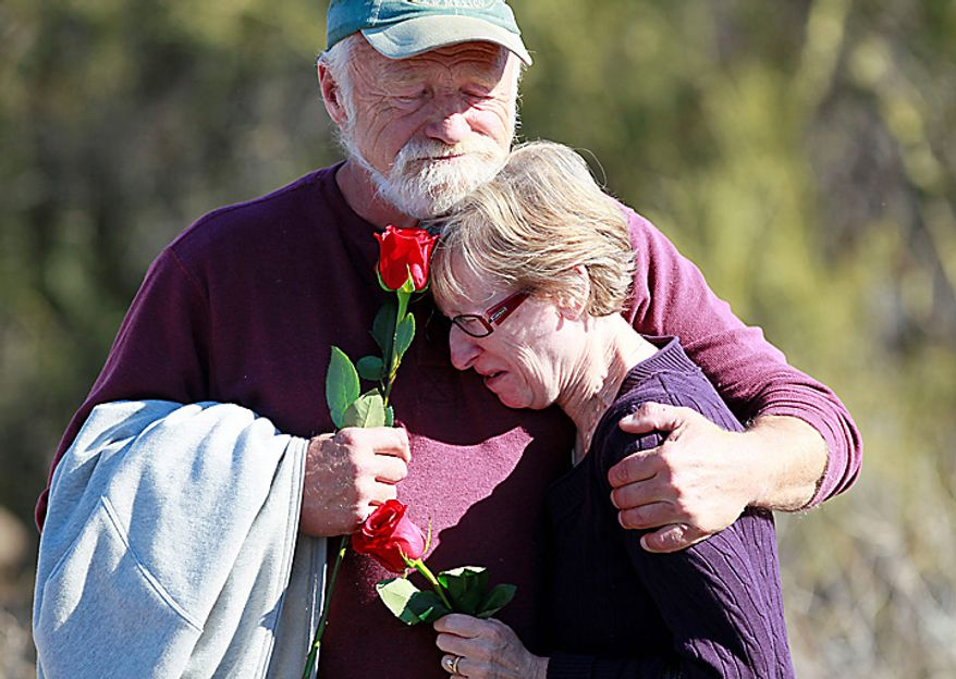Nicholas Darochkin and Ann Marie Kilargis of Tucscon, Ariz., hold each other outside St. Elizabeth Ann Seton Church at the funeral of 9-year-old Christina Taylor Green Thursday, Jan. 13, 2011, in Tucson, Ariz. Green was the youngest victim of Saturday's shooting in Tucson. (AP Photo/The Arizona Republic, Rob Schumacher)