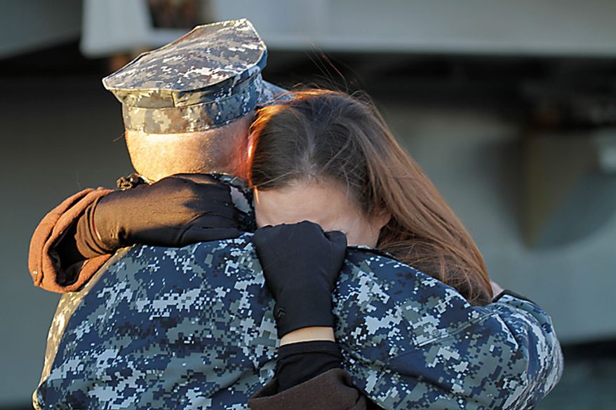 Petty Officer 3rd class, Robert Hampton, of Newport news, Va., gets a good bye hug from his wife, Rebecca, as he prepares to deploy on the nuclear powered aircraft carrier USS Enterprise at Naval Station Norfolk in Norfolk, Va., Thursday, Jan. 13, 2011. The USS Enterprise is deploying without its former commander as Navy brass investigates bawdy, sexually themed videos he showed to thousands of crew members. (AP Photo/Steve Helber)