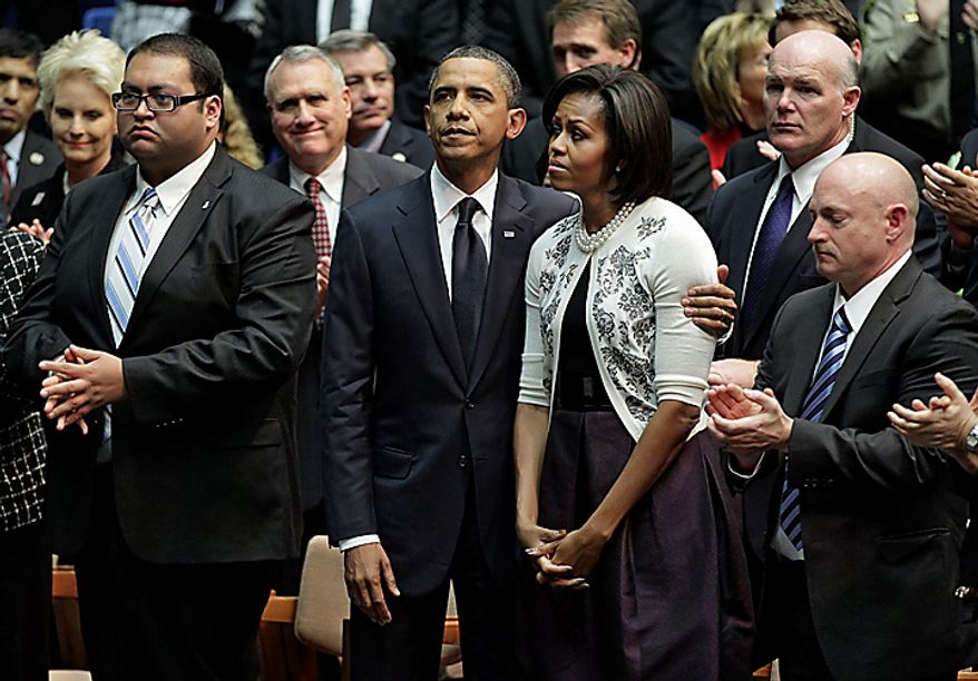 President Obama puts his arm around first lady Michelle Obama near the end of a memorial service in Tucson, Ariz., to honor the victims of a shooting rampage that killed six people and left 14 injured, including Arizona Congresswoman Gabrielle Giffords, on Wednesday, Jan. 12, 2011. (AP Photo/J. Scott Applewhite)