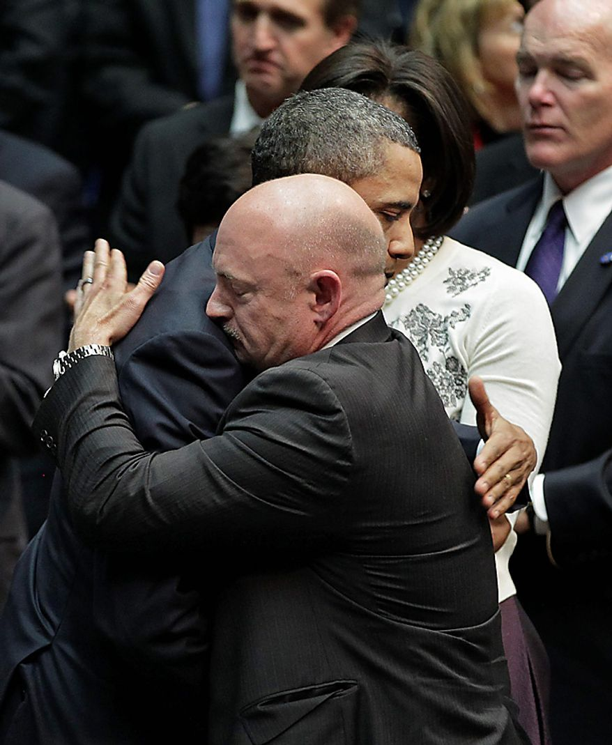 President Obama embraces Mark Kelly, the husband of critically wounded Rep. Gabrielle Giffords, at the end of a ceremony honoring the victims of a shooting rampage that killed six people and left 14 injured last Saturday, on the University of Arizona campus, Wednesday, Jan. 12, 2011. (AP Photo/J. Scott Applewhite)