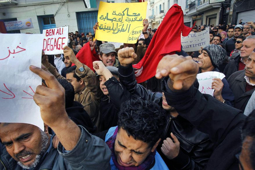 """Demonstrators hold placards reading """"Ben Ali get out"""" in Tunis, Friday, Jan. 14, 2011. Thousands of angry demonstrators marched through Tunisia's capital Friday, demanding the resignation of the country's autocratic leader a day after he appeared on TV to try to stop deadly riots that have swept the North African nation. (AP Photo/Christophe Ena)"""