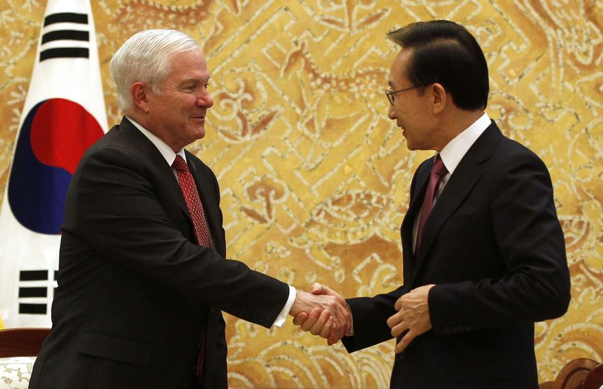U.S. Secretary of Defense Robert Gates, left, shakes hands with South Korea's President Lee Myung-bak at the Blue House in Seoul, South Korea, on Friday, Jan. 14, 2011. (AP Photo/Larry Downing, Pool)