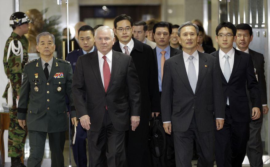 Defense Secretary Robert Gates, front left, and South Korean Defense Minister Kim Kwan-jin, front right, walk into the meeting room at the Defense Ministry in Seoul, South Korea, Friday, Jan. 14, 2011. (AP Photo/ Lee Jin-man, Pool)