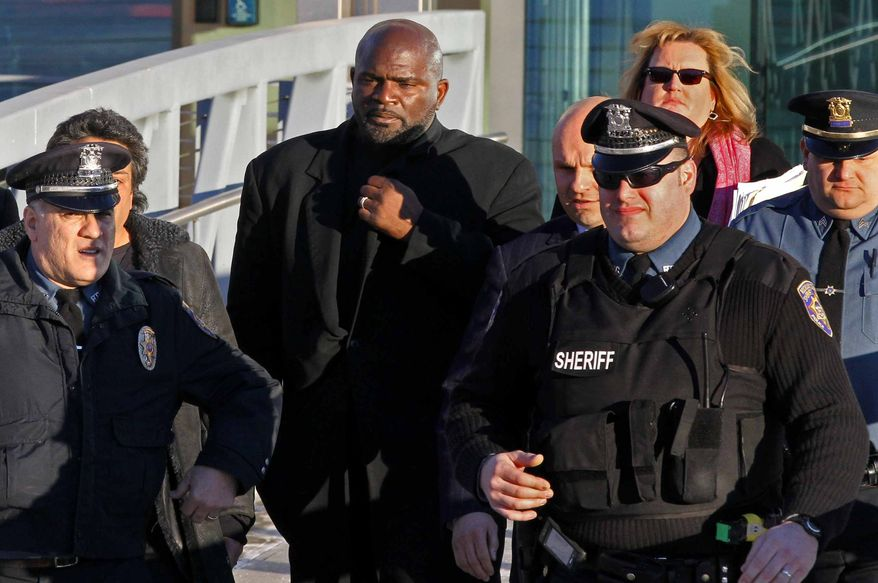 Former NFL footbal star Lawrence Taylor, center, is escorted from the Rockland County Courthouse on Thursday, Jan. 13, 2011, in New City, N.Y., after he pleaded guilty to misdemeanor charges of sexual misconduct and patronizing a prostitute. The 51-year-old ex-linebacker will get no jail time following his plea Thursday. He is required to register as a sex offender. (AP Photo/Craig Ruttle)