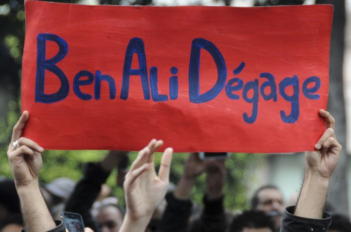"Protesters hold a banner reading ""Ben Ali get out"", calling for the resignation of Tunisia's President Zine El Abidine Ben Ali, in the capital, Tunis, Friday, Jan. 14,2011. (AP Photo)"
