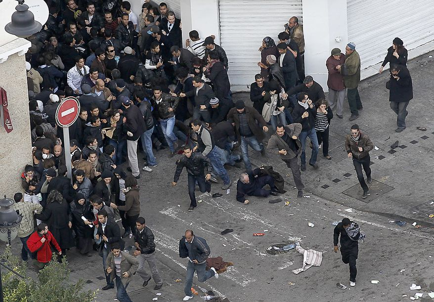 Protesters run to leave the demonstration as police throw teargas in Tunis, Friday, Jan. 14, 2011. Tunisia's president declared a state of emergency and announced that he would fire his government as violent protests escalated Friday, with gunfire echoing in the North African country's usually calm capital and police lobbing tear gas at protesters. (AP Photo/Christophe Ena)