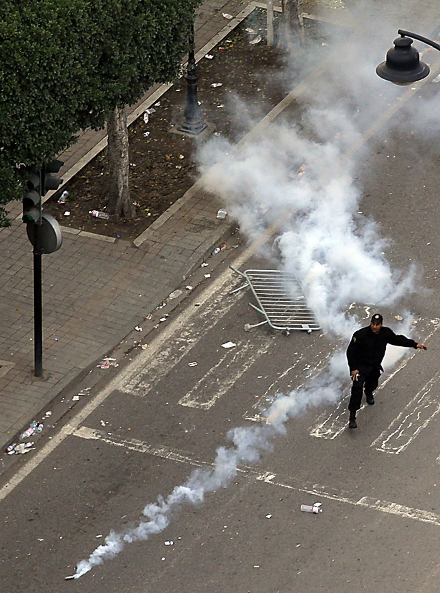 A police officer uses teargas during clashes in Tunis, Friday, Jan. 14, 2011. Tunisia's president declared a state of emergency and announced that he would fire his government as violent protests escalated Friday, with gunfire echoing in the North African country's usually calm capital and police lobbing tear gas at protesters. (AP Photo/Christophe Ena)