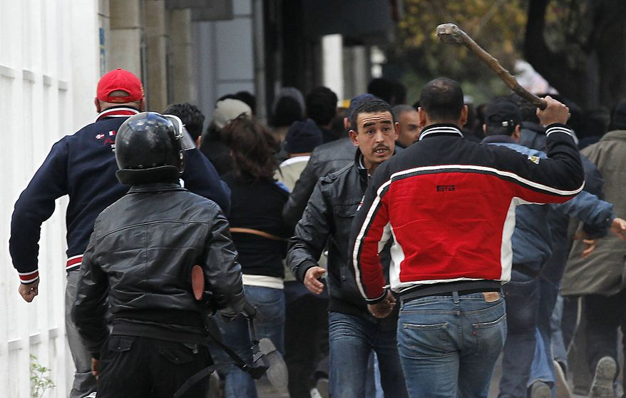 Plain clothed police and riot police officers clash with demonstrators in Tunis, Friday, Jan. 14, 2011. Tunisia's president declared a state of emergency and announced that he would fire his government as violent protests escalated Friday, with gunfire echoing in the North African country's usually calm capital and police lobbing tear gas at protesters. (AP Photo/Christophe Ena)