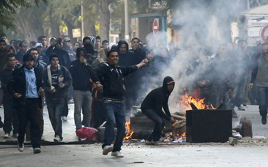 Demonstrators  throws stones at police during clashes in Tunis, Friday, Jan. 14, 2011. Tunisia's president declared a state of emergency and announced that he would fire his government as violent protests escalated Friday, with gunfire echoing in the North African country's usually calm capital and police lobbing tear gas at protesters. (AP Photo/Christophe Ena)