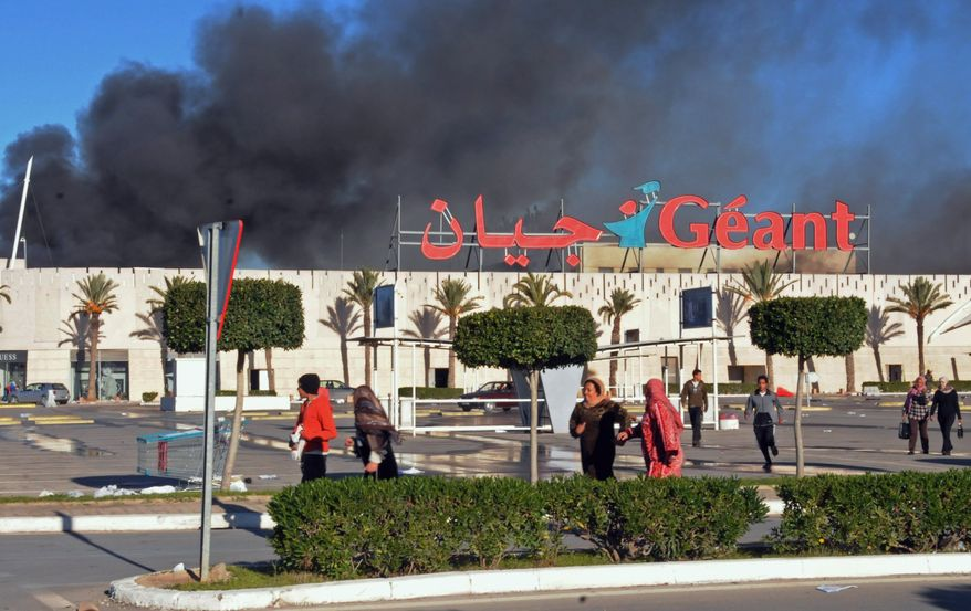 A supermarket is on fire after it was sacked and looted in Bizerte, Tunisia, on Saturday, Jan. 15, 2011. The Tunisian capital's main train station has been burned to the ground, and shops have been sacked and looted in violence that came after the North African nation's president fled the country. (AP Photo/Hassene Dridi)